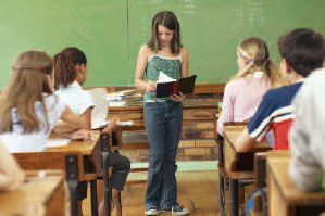 Female student standing in front of class reading her book